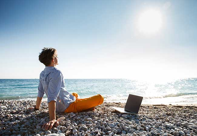 man on beach with laptop